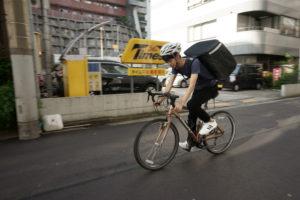 自転車で疾走するデリバリーの配達員